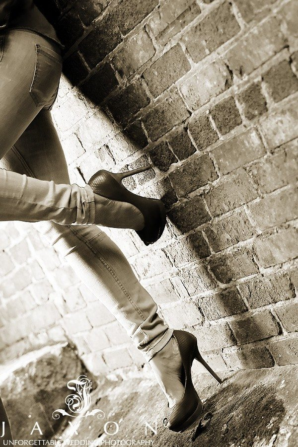 sepia photo of woman's stilettos as she stands leaning against a brick wall