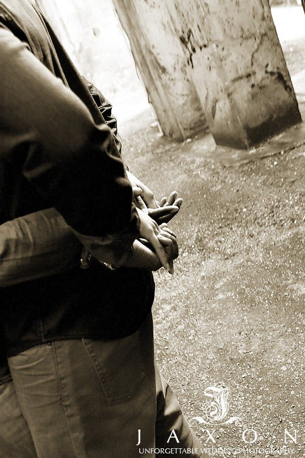 Sepia photograph of couple fingers intertwined behind his back