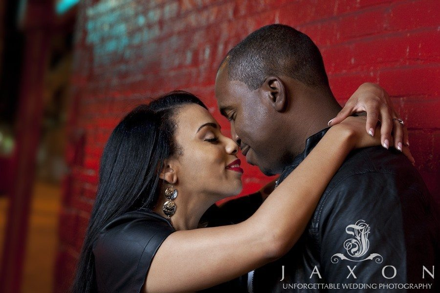 Couple nose to nose while leaning aging a red brick wall