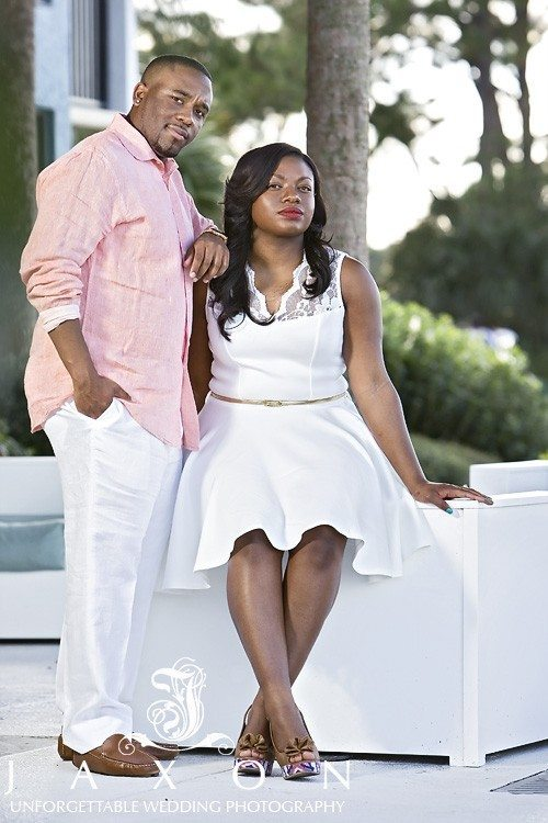 Couple in white and pink on the grounds of Sandestin Resort during their engagement session