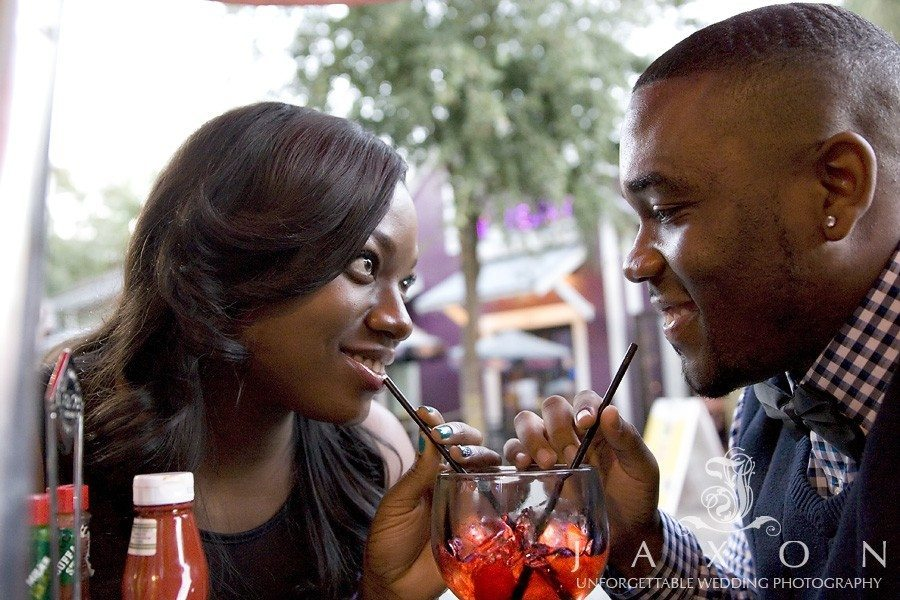 Couple sharing a cocktail during their engagement photo session