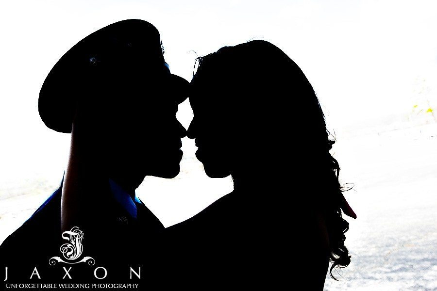 a silhouette of the couple smiling and touching noses as she raises his cap
