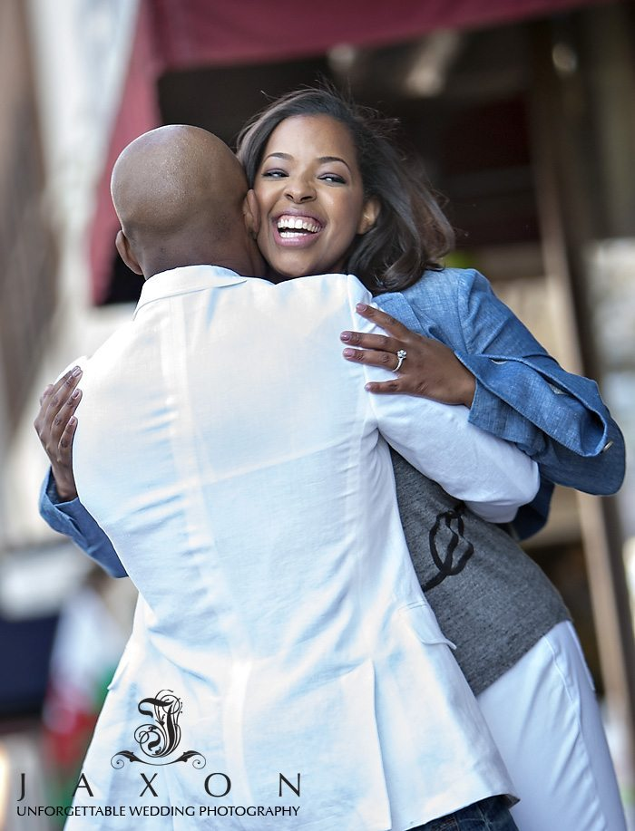 The couple shares a hearty laugh as they embrace during their Marietta Square Engagement Session