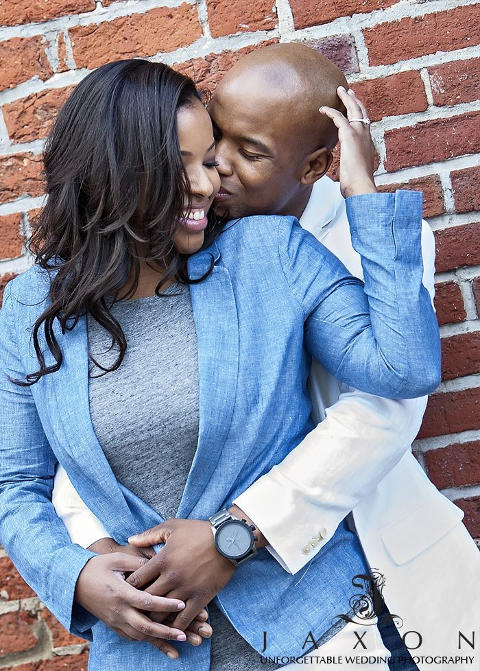 a steamy romantic embrace with the red brick wall as a backdrop, her blue sports blazer and his white contrasts beautifully