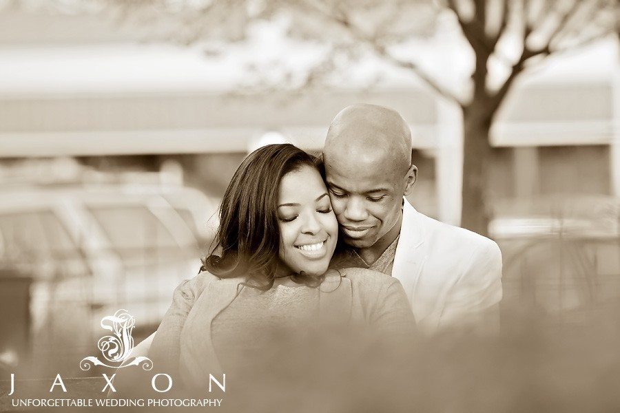 a warm embrace whilst sitting on a bench in Grover Park during their Marietta Square engagement session