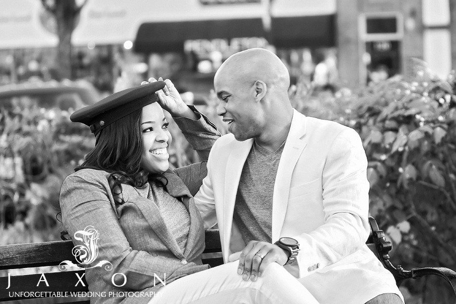 She shares his military hat playfully on a park bench during their Marietta Square Engagement Session