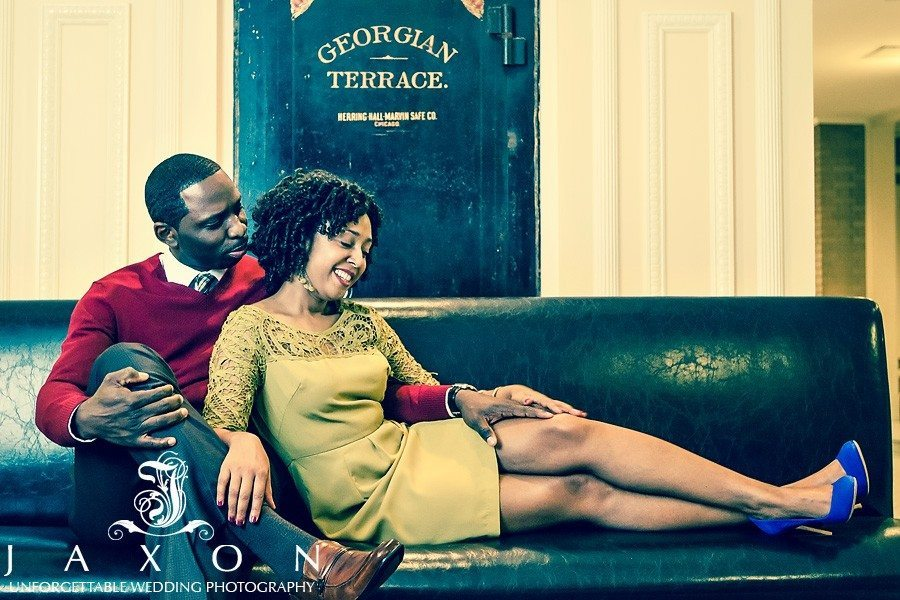 couple on a vintage couch in the cellar at their Georgian Terrace hotel engagement session