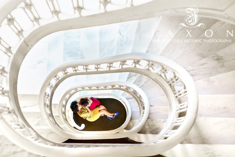 he sweeps her up in his arms at the bottom of the spiral staircase during their Georgian Terrace Hotel engagement session