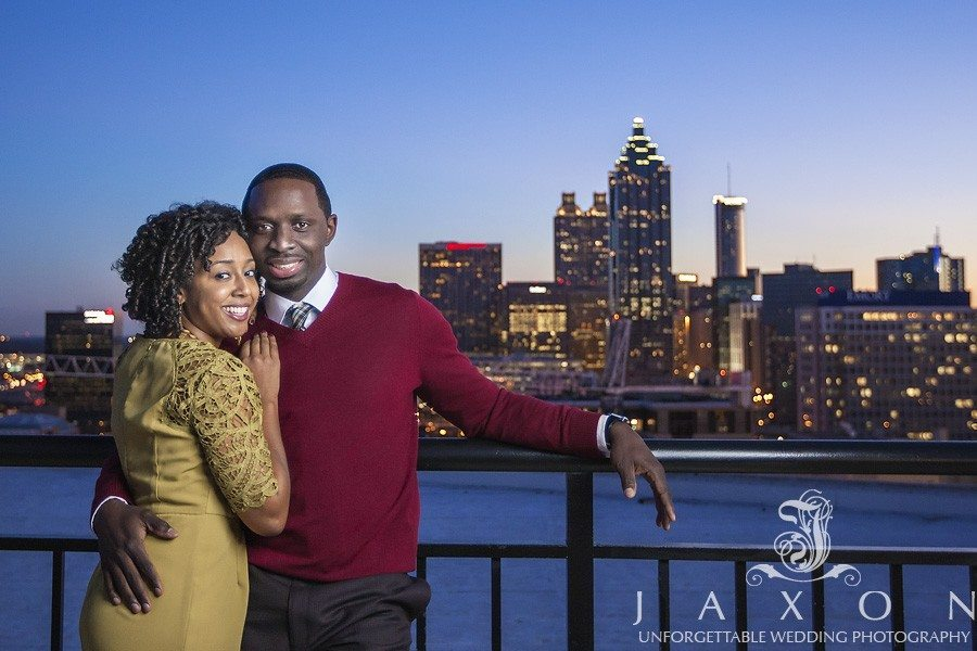 a roof top twilight portrait with the last embers of sunlight kissing the downtown Atlanta buildings in the background during their Georgian Terrace Hotel engagement session
