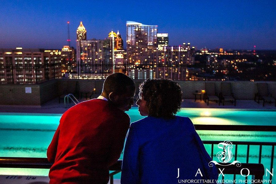 Couple gets close on the Roof top during Georgian Terrace Hotel engagement session, the midtown Atlanta sparkles in the background in this night time photograph