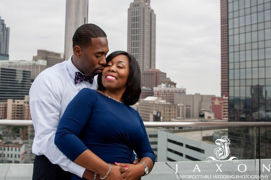 Couple on the roof top at the Glenn Hotel with Atlanta City skyline as backdrop