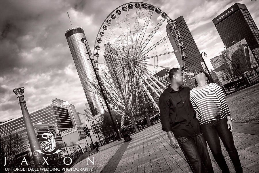 Couple enjys a laugh at centennial olympic park with the ferris wheel in the background