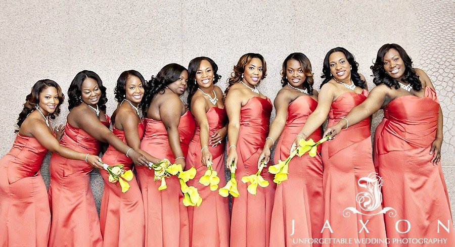 Bridesmaids in salmon pink dresses and yellow calla lilies vogue for the camera