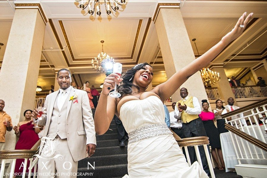 jubilant bride salutes her admiring guests as the groom looks on