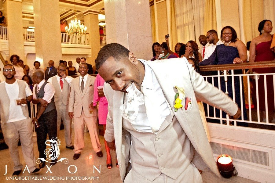 groom gets ready to toss the garter after removing it with his teeth
