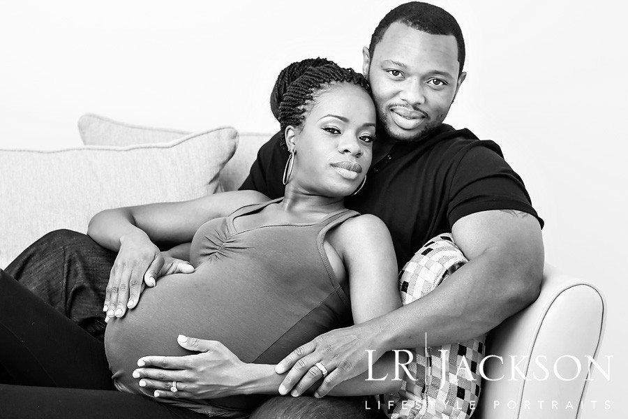 Maternity   In this black and white portrait the expecting parents lay on couch