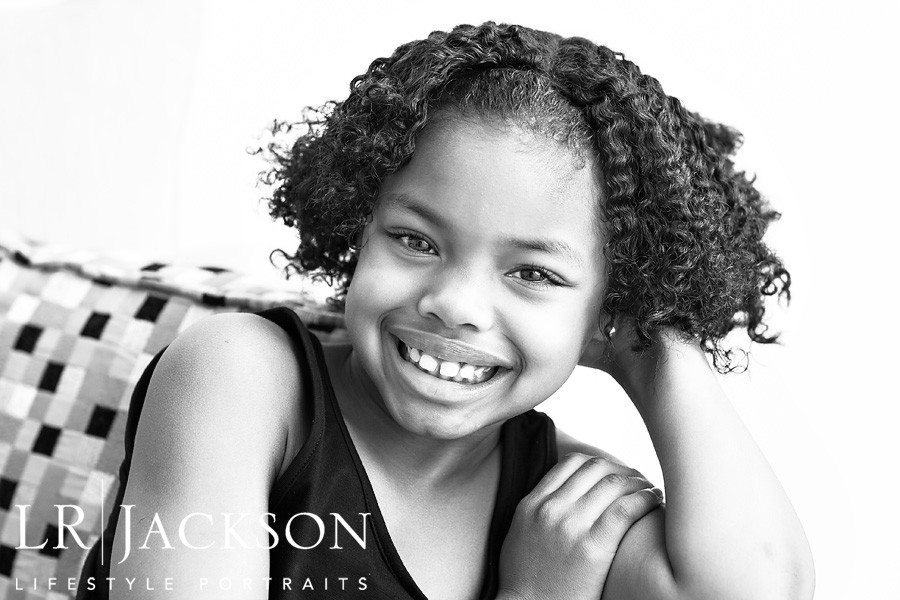 B&W portrait of you girl with curly hair at her home