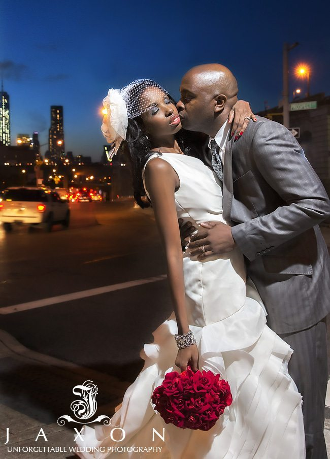 Bride and groom embraces in the streets next to Brooklyn Bridge Park in this late evening photograph   Riviera Wedding Brooklyn, NY