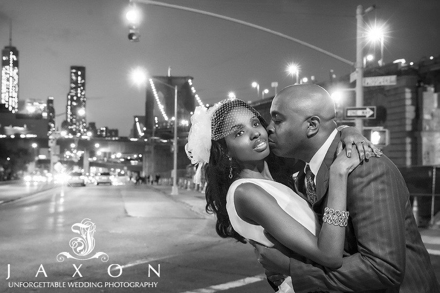 In this night time b&w photograph the groom kisses his bride, the Brooklyn Bridge and mManhattan skyline could be see in the distance   Riviera Brooklyn