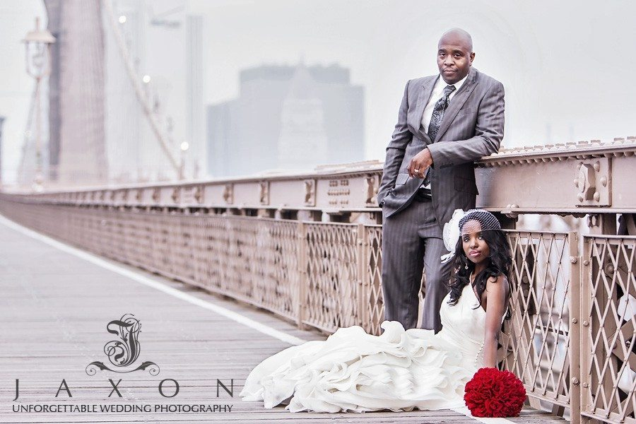 Bride sits on and groom stands leaning on the Brooklyn Bridge railing NY   Riviera Wedding Brooklyn, NY