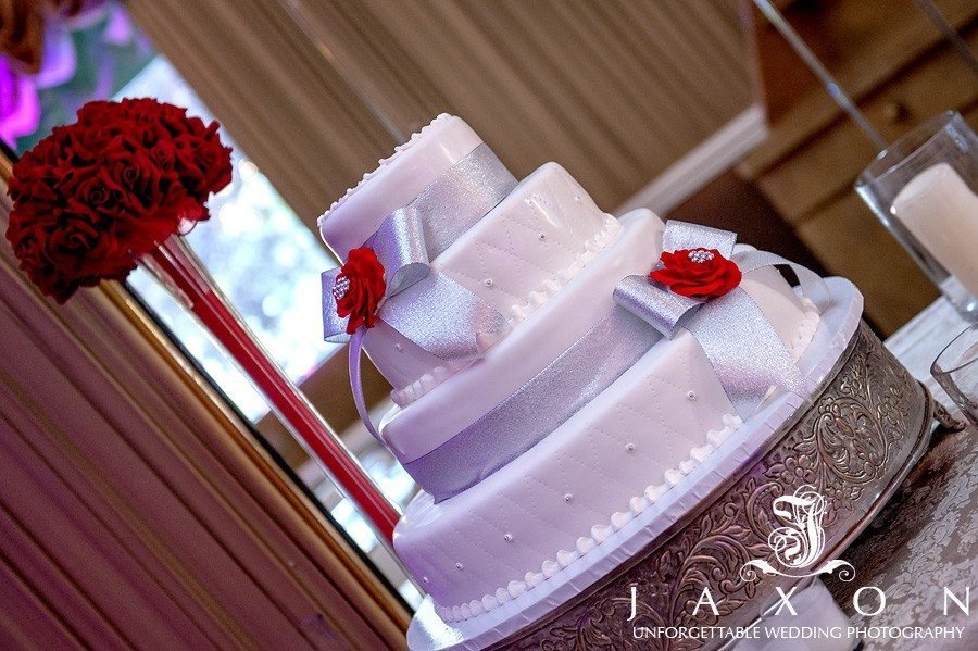 Four tiered round wedding cake embellished with two silver ribbons with bows and a red rose   Riviera Wedding Brooklyn, NY