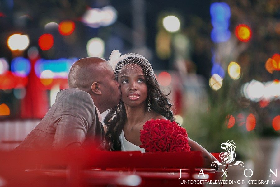 In this night time photograph the bride and groom sits at a table in Times Sq NY the couple and her red bouquet stand out against the blurred multi colored lights of times square   Riviera Wedding Brooklyn, NY