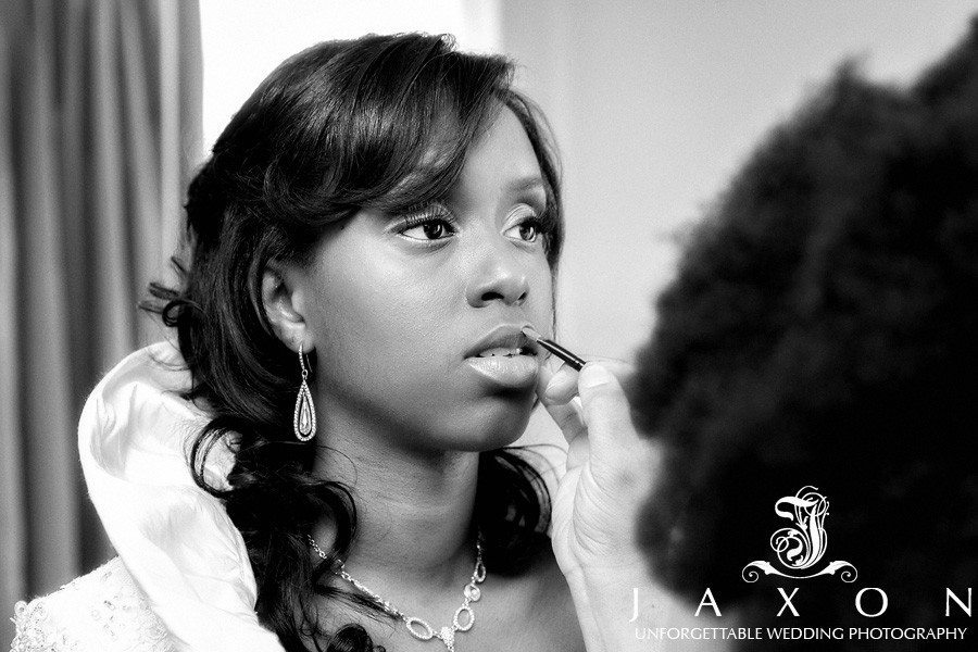 in their black and white photograph the Bride is having her makeup applied