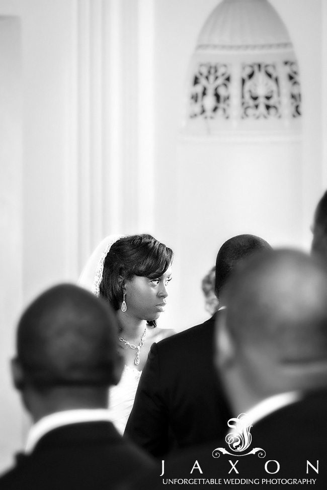 this black white photograph captures the bride looking intently at the minister during the wedding ceremony in the imperial ballroom