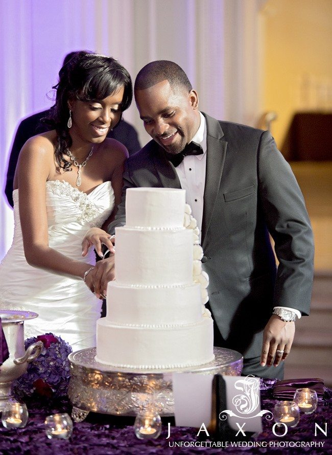 Couple smiles as they cut the wedding cake