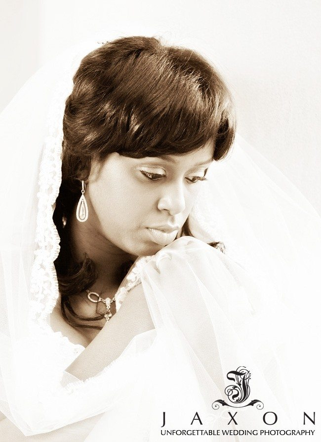 Moody portrait of the bride wrapped in her veil