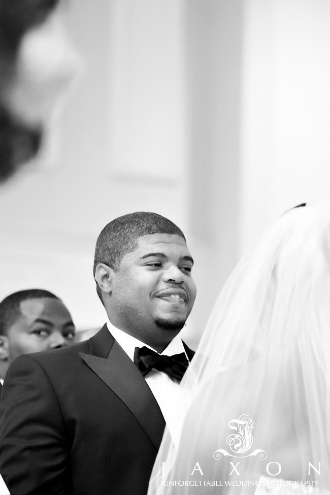 A smiling groom exchanges vows during ceremony in the Piedmont Ballroom at the Georgian Terrace in Atlanta, in this black and white photograph