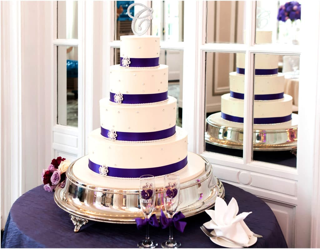 Four tier round white wedding cake with purple ribbon accented with pearls and broach
