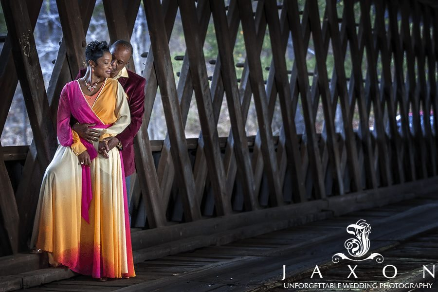 couple embraces inside the quaint and historical pine and cedar Covered Bridge leading to Indian Island