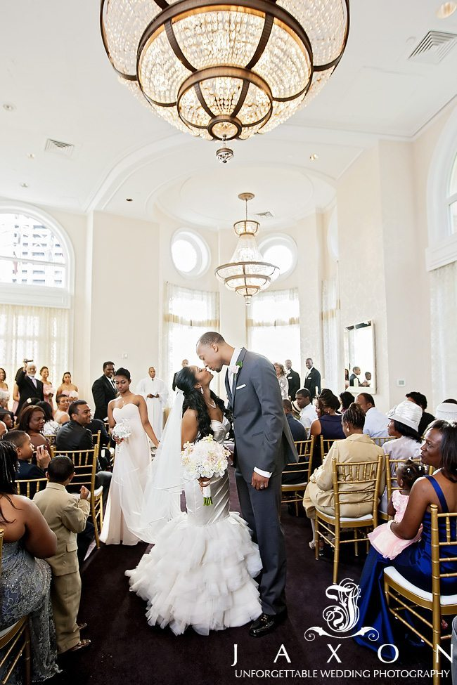 Bride and groom kisses at the end of wedding ceremony in Mitchell Ballroom at Georgian Terrace Hotel