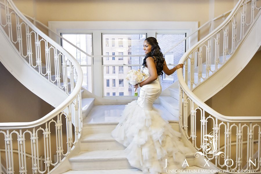Bride hold Unique Floral Expressions rose bouquet on the spiral staircase