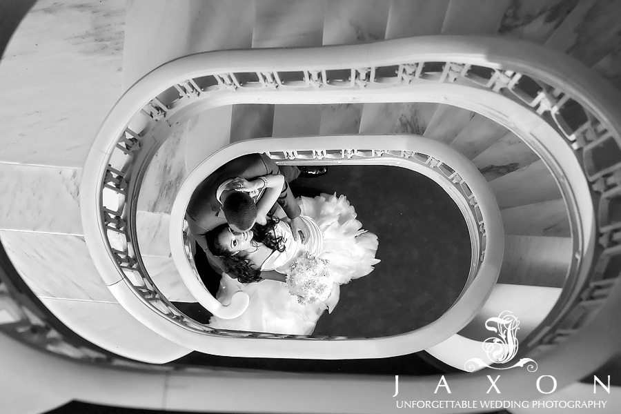 B&W portrait of Bride and groom between the spiral staircase