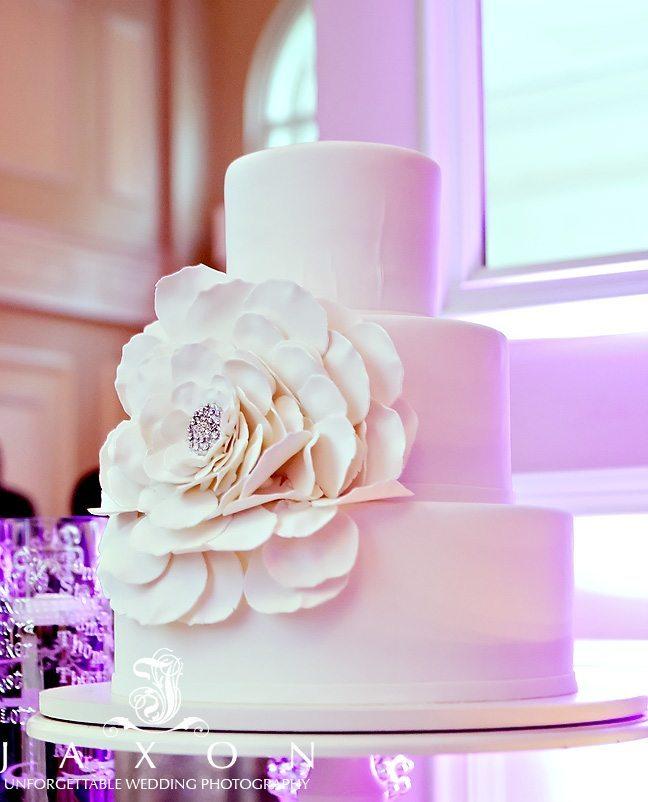 Three tiered white round wedding cake with large white flower