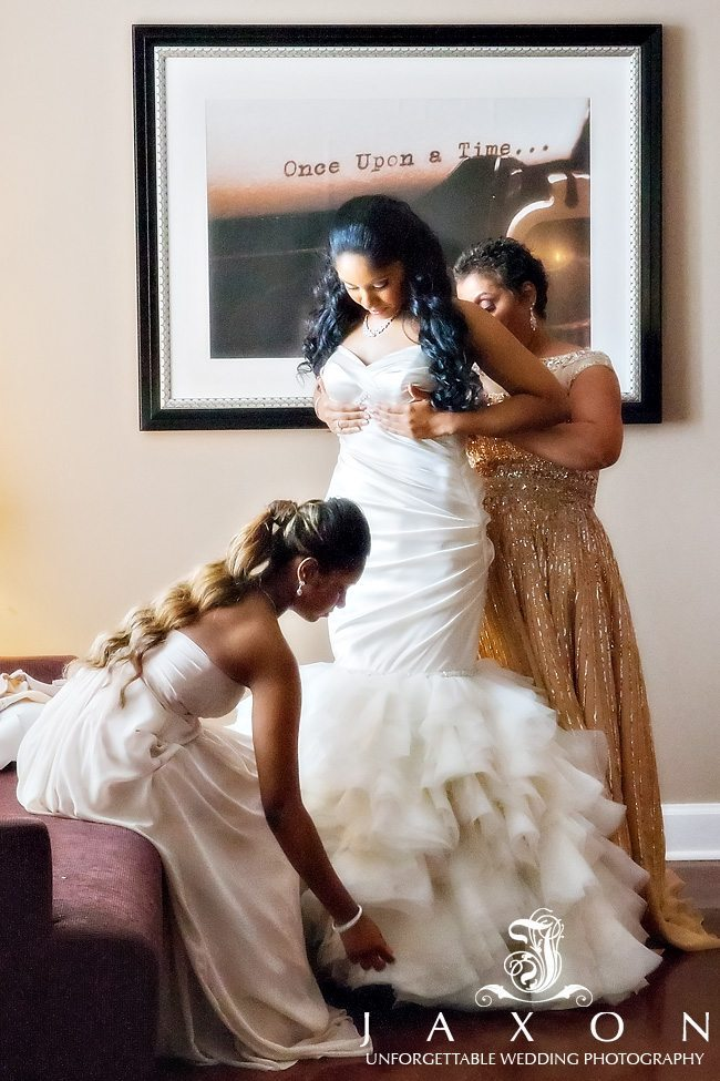 Bride being helped into her dress at the Georgian Terrace