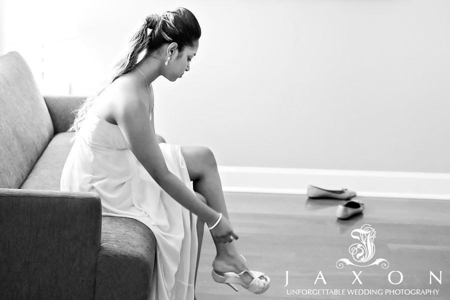 B&W photo of the Maid of honor lacing up her shoes