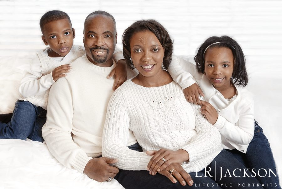 family photographed in matching cream long sleeved sweaters and jean bottoms