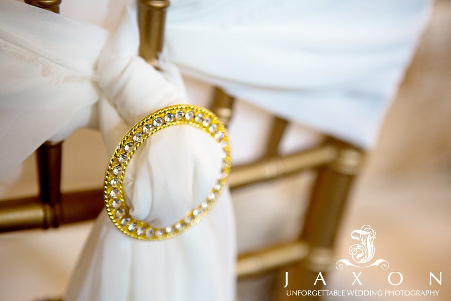 One of the dining chairs decorated with a white cloth wrapped around it and fastened by a round gold Broach