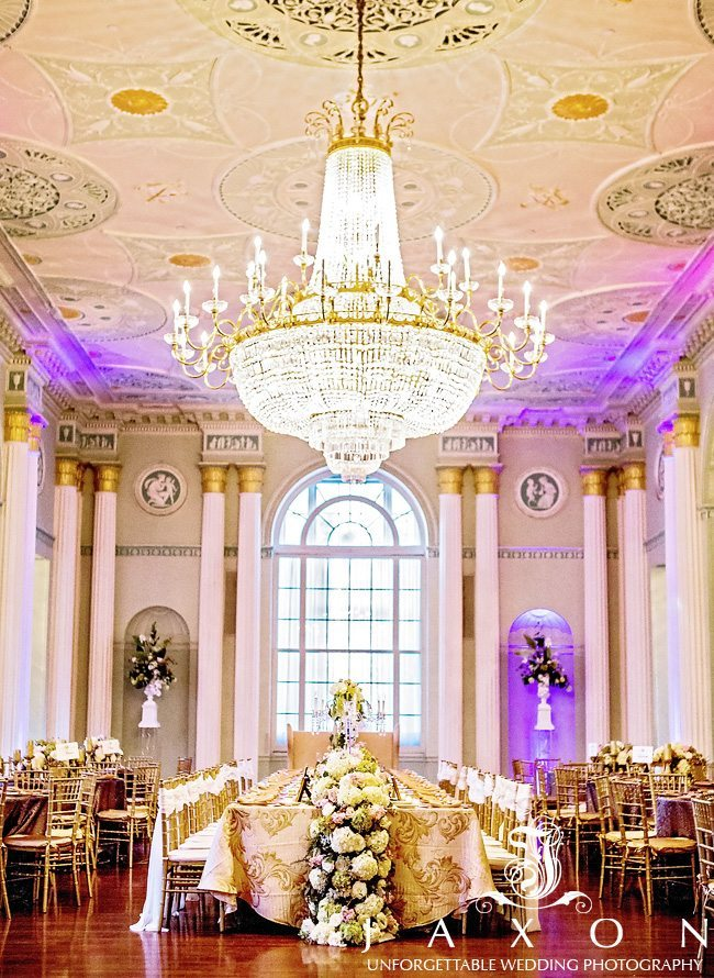 The grand Georgian ballroom at the Biltmore Ballrooms with a dazzling hanging crystal chandelier, floor to ceiling columns and estate style dining table with white flowers cascading down the side.