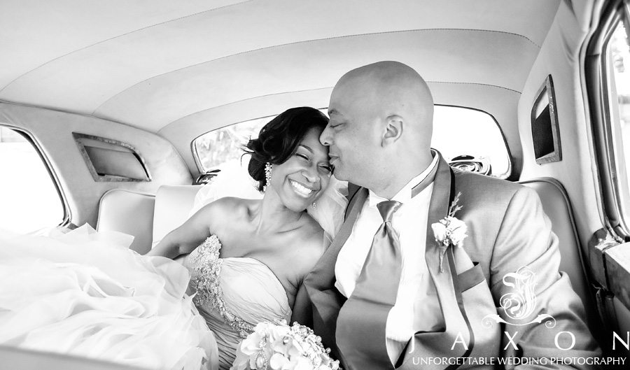 A b&W of couple, smiling with excitement and her groom kissing her forehead in sheer adoration, in the backseat of the vintage rolls royce.