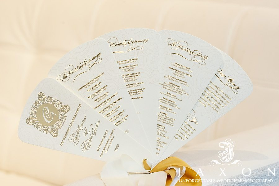 The lovely fanned out wedding ceremony program styled with beautiful gold calligraphy and held together by gold and white ribbons