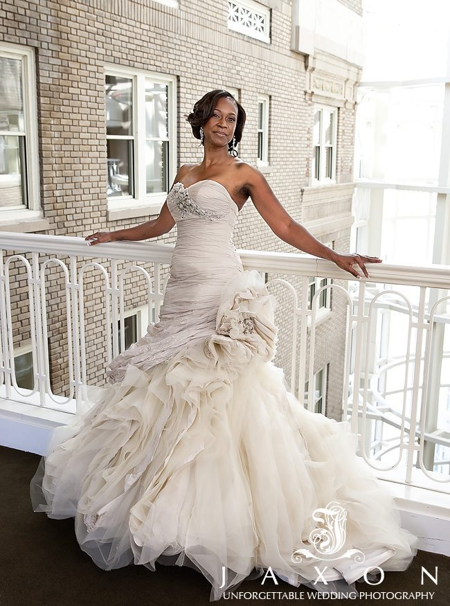 The beautiful bride leaning against a white balcony looking very poised and beautiful in her stunning gown adorned with rhinestones at the bust and left hip