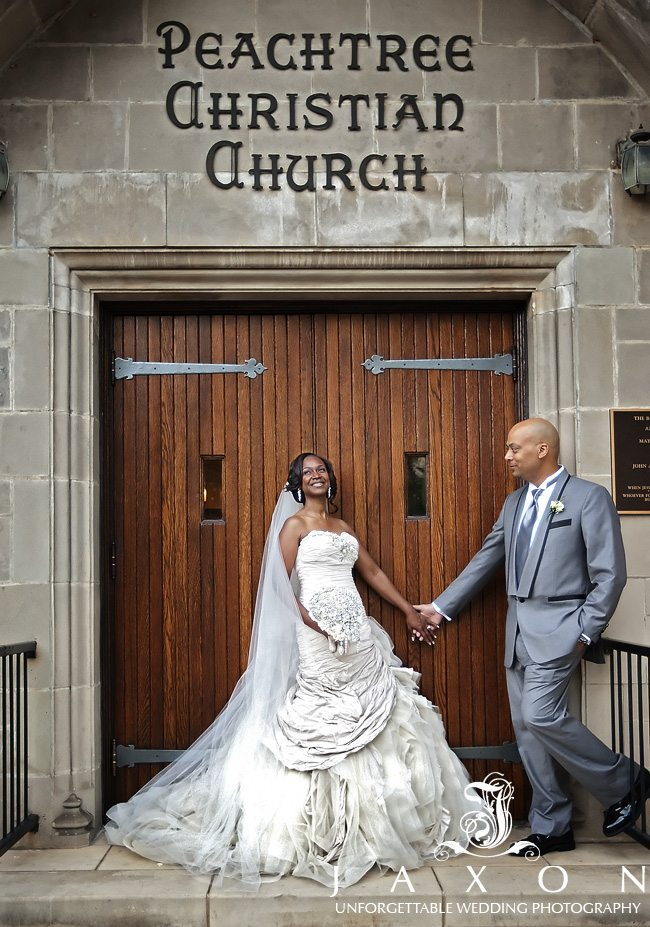 The happy bride holds her husband's hand outside the doors of the PeachTree Christian Church
