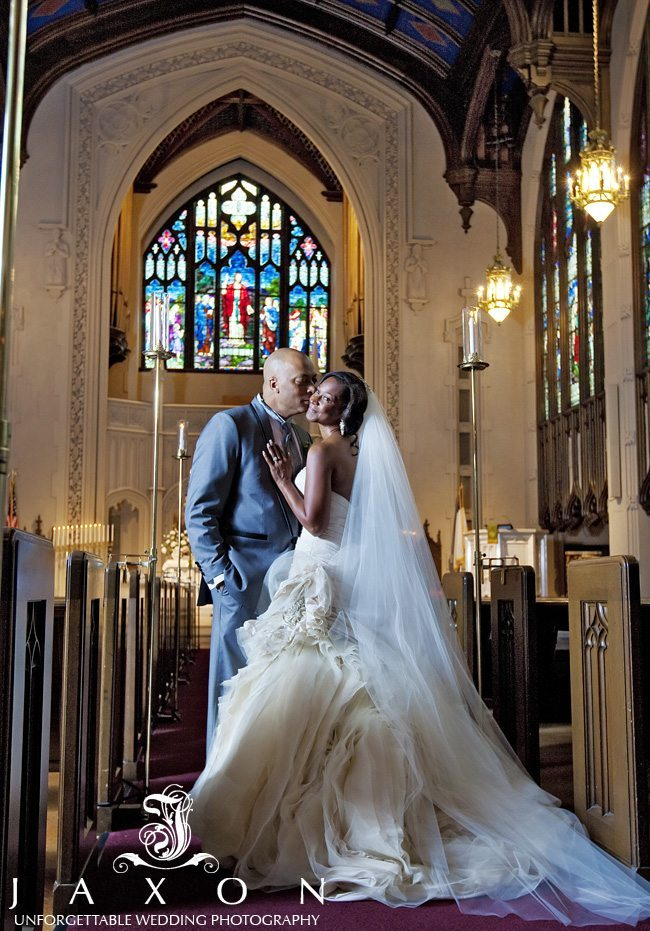 The groom kissing his beautiful bride, in the aisle, with her cathedral veil flowing elegantly behind her