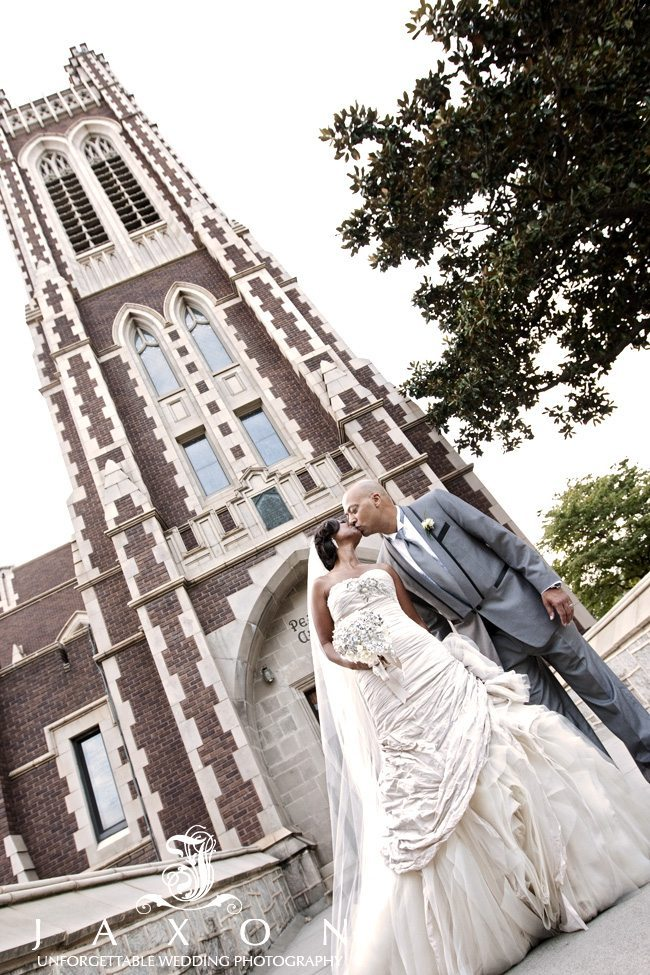 The handsome couple smooches each other with the Peach Tree Christian Church Tower in the background