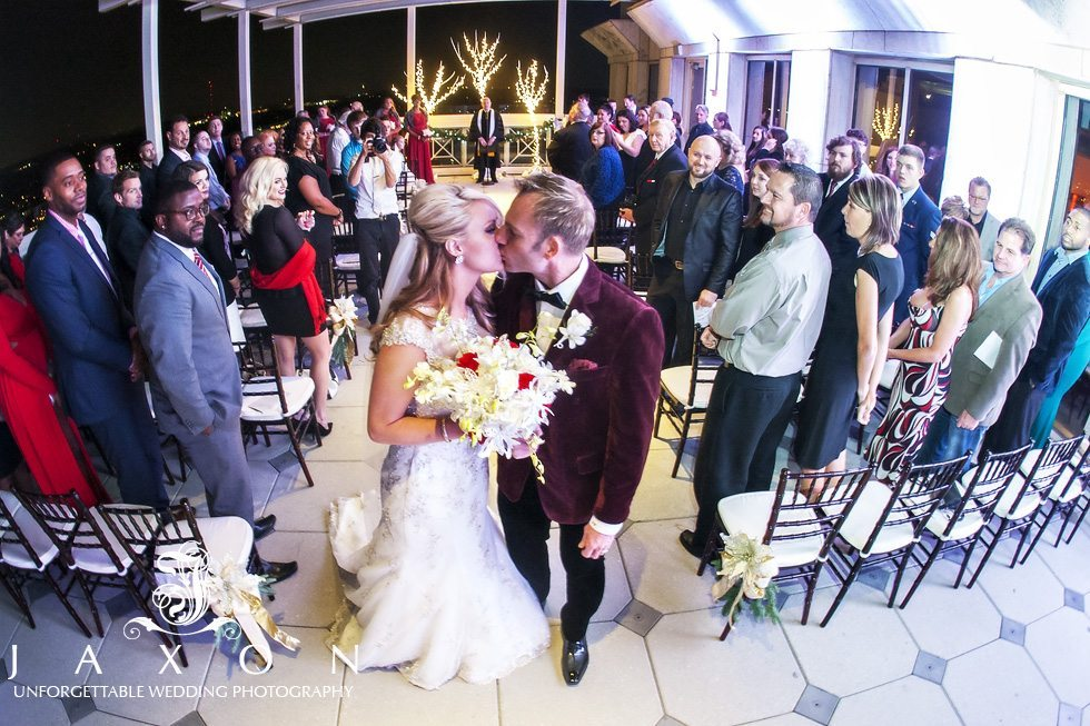 Bride and Groom exits wedding ceremony with a kiss as their guests looks on at the end of their Peachtree Club Rooftop Wedding