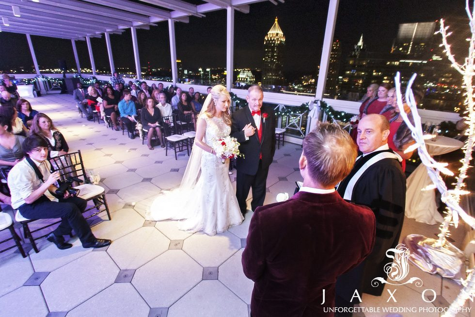 Father escorts bride into her wedding ceremony on the rooftop of the Peachtree club, high rise buildings glimmers in the night sky
